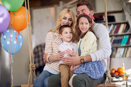 A young happy family is posing for a photo while sitting on the swing in a relaxed atmosphere at home. Family, home, playtime