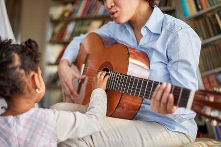 A cute little girl is so interested in her mother guitar playing while spending time in a relaxed atmosphere at home together. Family, home, playtime