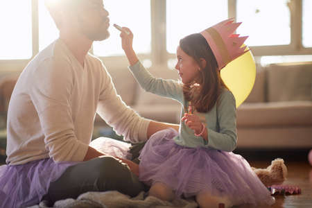 A young father enjoys when his little daughter ballerina  puts a lipstick on his lips while they are preparing for a ballet training in a relaxed atmosphere at home. Family, ballet, training