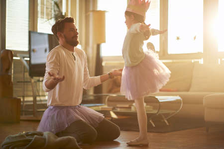 A young father correcting his little ballerina posture while they have a ballet training in a relaxed atmosphere at home. Family, ballet, training Standard-Bild