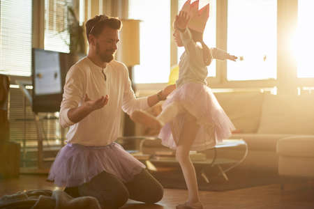 A little ballerina practicing a ballet move at a training in a relaxed atmosphere at home with a help of her father. Family, ballet, training