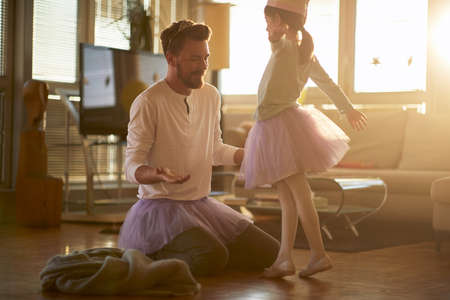A little ballerina practicing a ballet move at a training in a relaxed atmosphere at home with a support of her father. Family, ballet, training Standard-Bild
