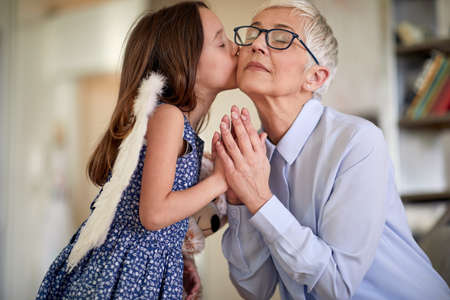 A little girl with angel wings is kissing and exchanging emotions with her grandmother in a family atmosphere at home. Family, home, love, playtime Standard-Bild