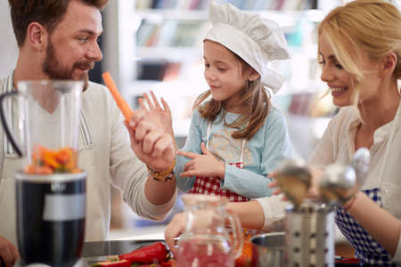 A young family is preparing the vegetables for a meal they are making in a cheerful atmosphere at home together. Family, home, kitchen Standard-Bild