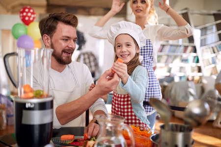 A little girl and her father posing for a photo while preparing a meal in a cheerful atmosphere at home together. Family, home, kitchen