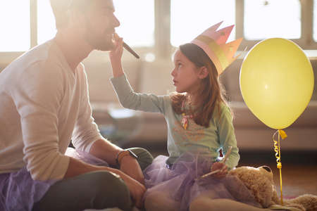 A little ballerina who puts makeup on her father's face while they are preparing for a training in a relaxed atmosphere at home. Family, ballet, training Standard-Bild