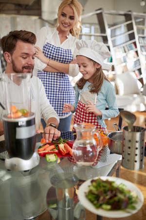 Joyful caucasian parents cooking with daughter at home Standard-Bild