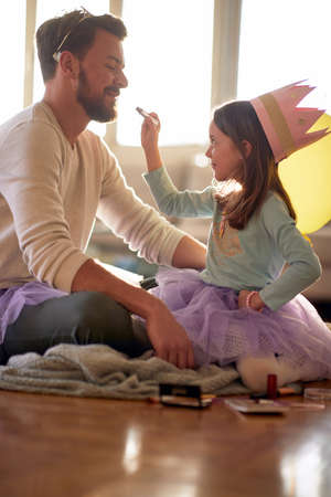 A little girl wants to put a make up on her father's face while they are preparing for a ballet training in a relaxed atmosphere at home. Family, ballet, training