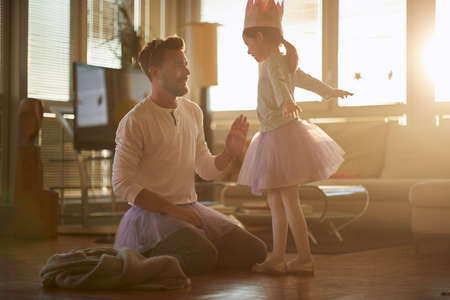 A young father is giving a support to his little ballerina while they having a ballet training in a relaxed atmosphere at home. Family, ballet, training