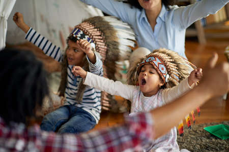 Children with indian war bonnets are raising their hands and yelling while imitating Indians with their parents in a cheerful atmosphere at home. Family, home, playtime Stock Photo
