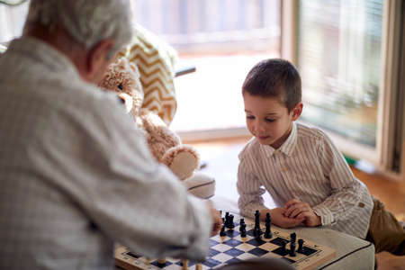 A little grandson enjoy playing a chess game with his grandpa in a relaxed atmosphere at home. Family, home, playtime Standard-Bild