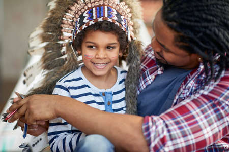 Joyful afro american dad and son playing together at home