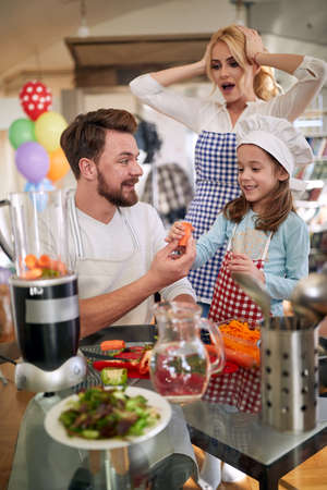 A young mother is worried that her husband and little daughter will destroy a meal they are preparing in a cheerful atmosphere at home. Family, home, kitchen