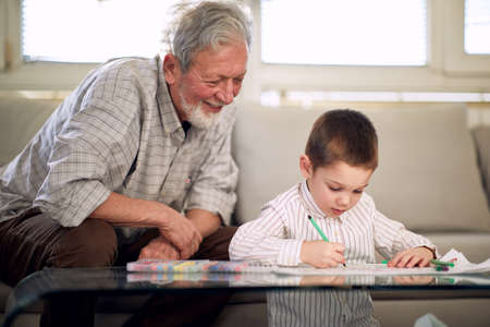 A grandpa watching his grandson drawing while they having a good time in a relaxed atmosphere at home together. Family, home, playtime