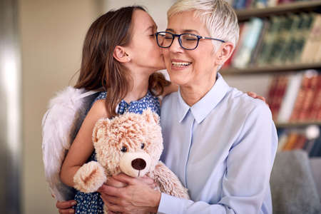 A happy grandma enjoys kisses and emotions getting from her little granddaughter in a family atmosphere at home. Family, home, love, playtime Standard-Bild