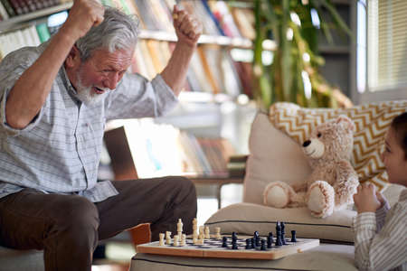 A happy grandpa enjoys playing a chess game with his little grandson in a relaxed atmosphere at home. Family, home, playtime
