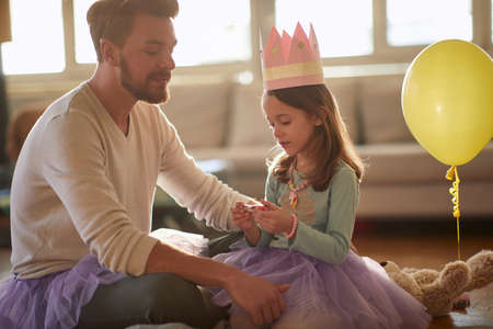 Happy dad and daughter dressing up toghether at home Standard-Bild