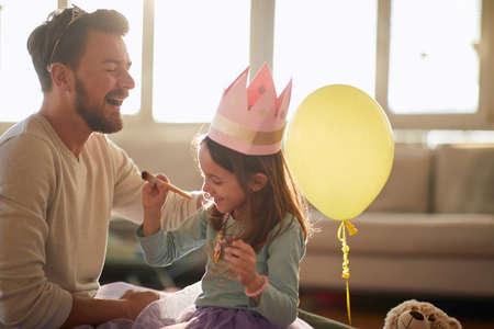 Joyful dad and daughter dressing up toghether at home Standard-Bild