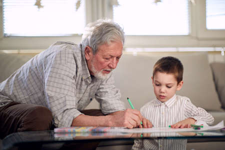 A grandpa showing his grandson how to draw while they having a good time in a relaxed atmosphere at home together. Family, home, playtime