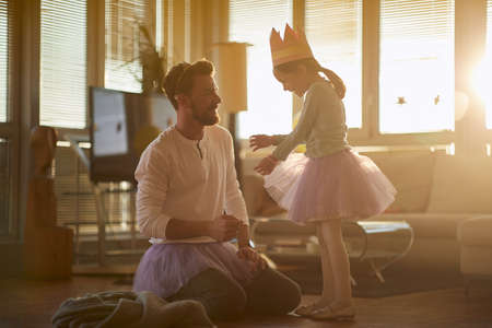 Dad and daughter dressing up toghether at home