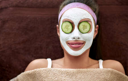 Smiling woman with cosmetic mask and cucumber on eyes, regeneration