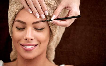 Beautiful young woman receiving professional make up