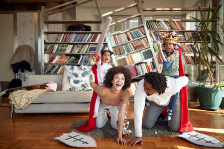 Cheerful afro american family playing together at home
