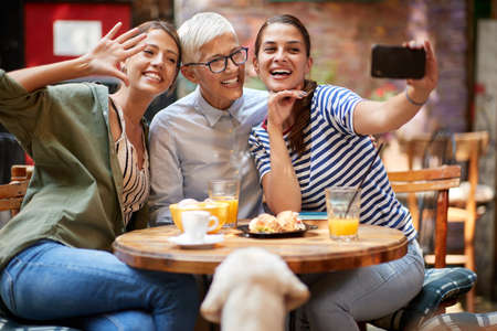 A group of female friends of different generations taking a selfie while they have a drink in a cheerful atmosphere in the bar together after long time. Leisure, bar, friendship, outdoor