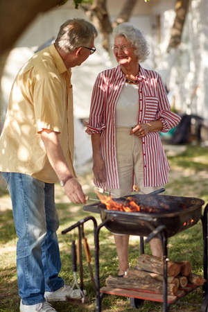 old caucasian couple making barbeque