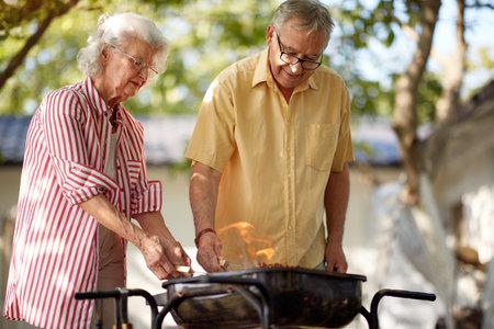 elderly caucasian couple making barbeque
