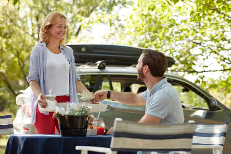 young beardy guy taking cup of coffee from a tray offered by beautiful caucasian blonde female