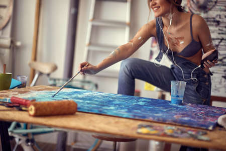 A young and attractive female artist is enjoying the music while painting in a relaxed atmosphere in her studio. Art, painting, studio