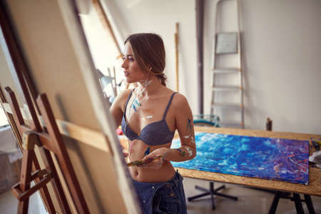 A young and attractive female artist in a bra is standing in front of the easel in a relaxed atmosphere in her studio and painting. Art, painting, studio