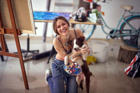 A young and attractive female artist in a bra is posing for a photo with her dog while taking a break from painting in a relaxed atmosphere in her studio. Art, painting, studio