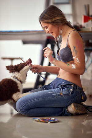 A young and attractive female artist in a bra is in a playtime with her dog in a relaxed atmosphere in the studio. Art, painting, studio