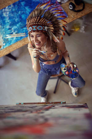 Bird-eye view of a young and attractive female artist with a war bonnet who is in a good mood while sitting in front of the easel and enjoying painting and listening to the music in a pleasant atmospher in the studio. Art, painting, studio Stock fotó