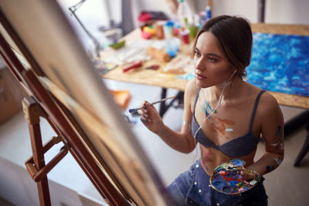 Close-up of a young and attractive female artist sitting in front of the easel and enjoying painting in a pleasant atmosphere in the studio. Art, painting, studio