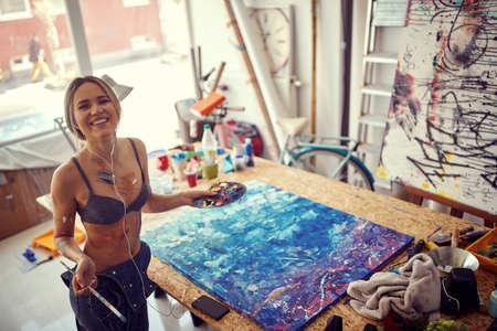 Bird-eye view of a young and attractive female artist posing for a photo while painting and listening to the music in a relaxed atmosphere in her studio. Art, painting, studio