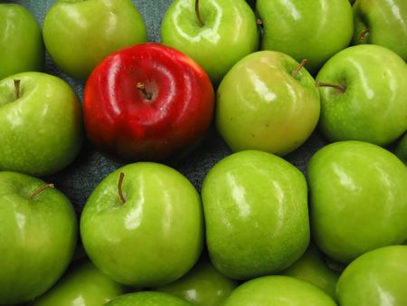 One red apple among lots of green apples