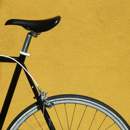 Black bike against yellow wall Stock Photo
