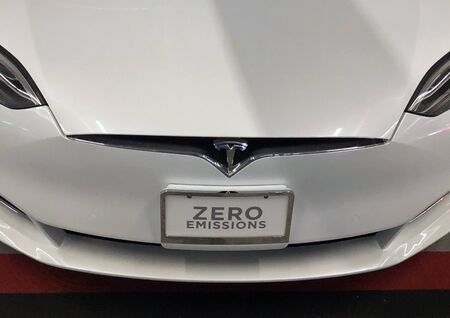 Grill of Tesla car with zero emissions sign