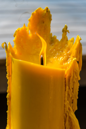 birthday religious: Yellow candle with flame and melting wax