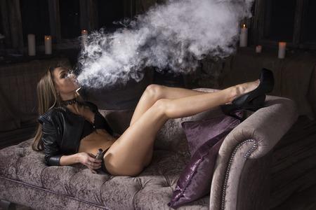 Sexy vrouw rokende elektronische sigaret en liggend op de bank