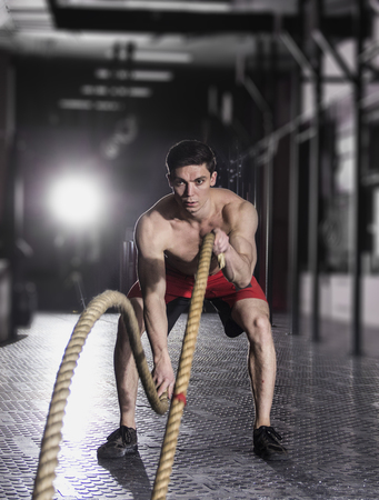 Muscular athlete with battle rope battle ropes exercise in the f Stock Photo