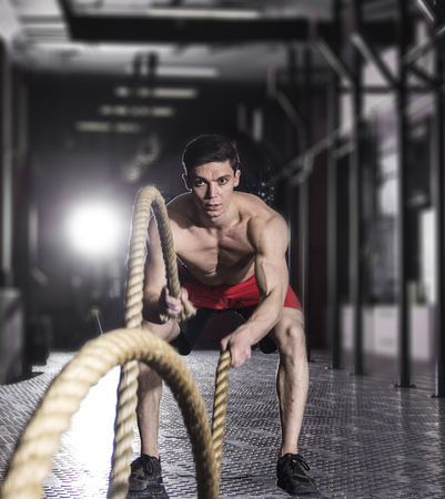 Muscular athlete with battle rope battle ropes