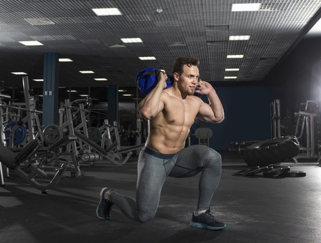 Attractive bodybuilder doing squats using fitness bag in modern Stock Photo
