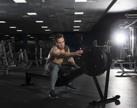 Muscular male athlete on rowing machine in modern fitness center Stock Photo