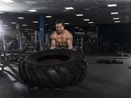 Muscular,Strong bodybuilder pushing tire in modern fitness cente