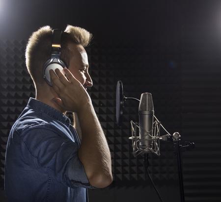 プロのスタッドで若い白人の歌手のレコーディング アルバム