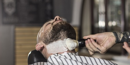 barber preparing to shave the beard in the barbershop.Close up image Stock Photo